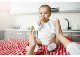母亲把手伸向坐在桌子上的可爱婴儿_9696745