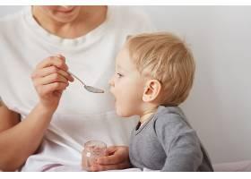 母亲用勺子喂她的男婴_10324050