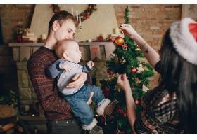 母亲用圣诞饰品分散婴儿的注意力而父亲则_982545