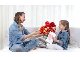 母亲节手持鲜花的小女儿祝贺她的母亲_10896579