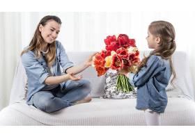 母亲节手持鲜花的小女儿祝贺她的母亲_10896580