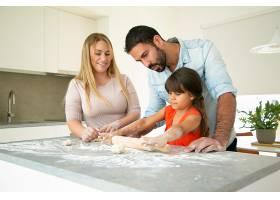 积极的父母看着女儿在厨房桌子上用面粉滚面_9650599