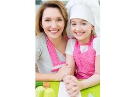 穿着粉色围裙的幸福微笑的母女在厨房里的肖_11599283