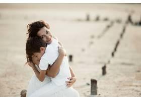 母子俩坐在沙滩上拥抱着穿着白色的衣服_7249523