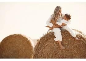 母子俩夏天在黄色的麦田上堆放干草或打_10885106