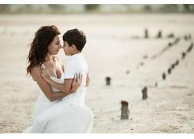 沙滩上可爱的母子肖像穿着白色的衣服看_7249524