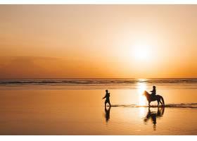 海滩上骑在马背上的年轻浪漫情侣的剪影肖像_8270057