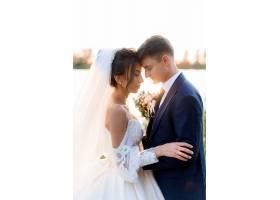 美丽的新娘和新郎闭着眼睛的肖像在傍晚的户_7498708