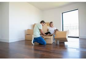 父母和孩子在新公寓里打开东西坐在地板上_11072768