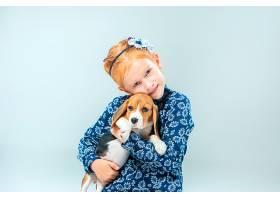 灰墙上快乐的女孩和一只小猎犬小狗_8821767