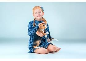 灰墙上快乐的女孩和一只小猎犬小狗_8821772