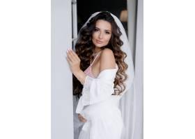 身穿白色丝绸长袍留着卷发的美丽长发黑发_7497112