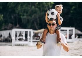 父子俩在海滩上踢足球_5507440