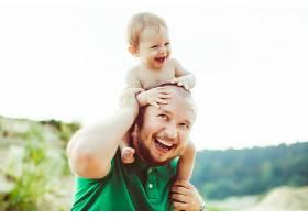 身穿绿色衬衫的父亲将年幼的儿子抱在脖子上_1234585