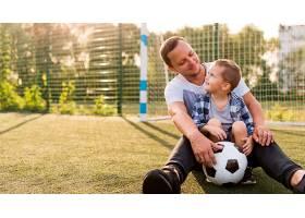 父子俩坐在足球场上_11176333