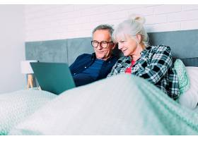 躺在床上拿着笔记本电脑的老年夫妇_2284869