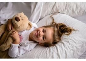 躺在床上的小女孩抱着柔软的玩具带着孩_9045690