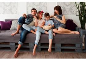 快乐的父母和他们的孩子坐在沙发上吃爆米花_5127620