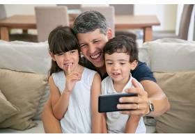 快乐的爸爸和两个孩子一起坐在家里的沙发上_9988483