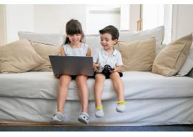 快乐的男孩和女孩坐在家里的沙发上使用笔_9988525