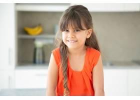 快乐的黑发拉丁小女孩穿着红色t恤在家里_9988467