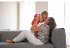 慈爱的母亲坐在沙发上满怀爱意地亲吻她的_11622930