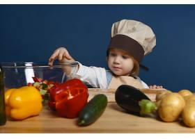戴着厨师帽的可爱小男孩站在厨房餐桌旁_10897560