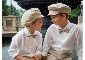 打着蝴蝶结戴着帽子的兄弟们坐在喷泉上_10119503