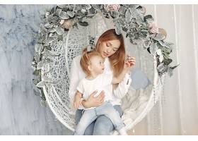 抱着婴儿坐在秋千上的女人穿着白衬衫的母_10705774