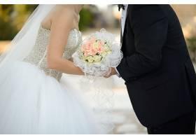新娘和新郎手持美丽的花束相互亲吻的特写镜_10110552