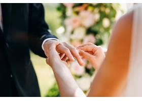 新娘把结婚戒指戴在新郎的手指上没有脸_3984957