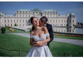 新郎在巨大的王宫前亲吻新娘的脖子_7497140