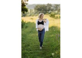 日落时分一名孕妇走在公园里_12967106