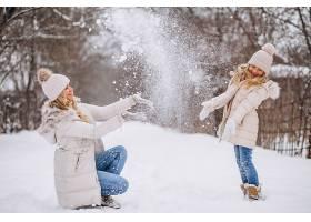 母亲和女儿一起在冬季公园散步_3964097