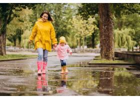 母亲和女儿在水坑里跳得很开心_8828095
