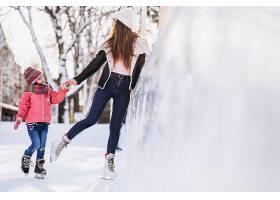 母亲和女儿在溜冰场上教滑冰_6641656