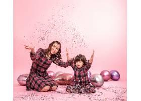 有趣的妈妈和孩子坐在粉色背景上小女孩和_9046230