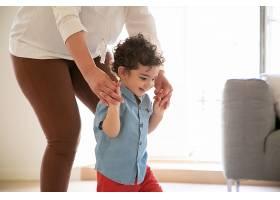 有趣的混血男孩在妈妈的帮助下学走路低头_11622664