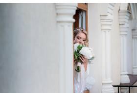 梦幻新娘手持婚礼花束站在大厅的柱子后面_2612591