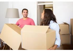 欢快的年轻拉丁夫妇在他们的新公寓里提着纸_10586110