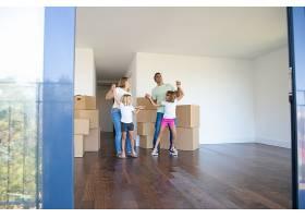 欢快的父母和女儿在搬进新公寓时在成堆的_10579289