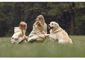 母亲和女儿在玩狗秋天公园的一家人宠物_11191003