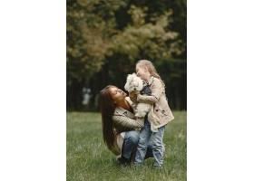 母亲和女儿在玩狗秋天公园的一家人宠物_11191124