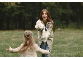 母亲和女儿在玩狗秋天公园的一家人宠物_11191165