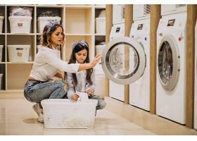 母亲和女儿在自助洗衣店洗衣服_6636863
