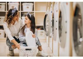 母亲和女儿在自助洗衣店洗衣服_6636871