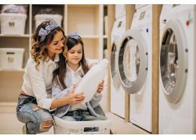 母亲和女儿在自助洗衣店洗衣服_6636872