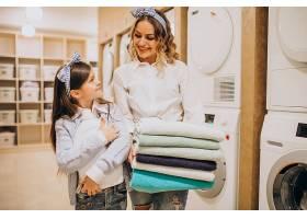 母亲和女儿在自助洗衣店洗衣服_6636885