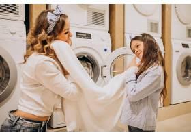 母亲和女儿在自助洗衣店洗衣服_6636890