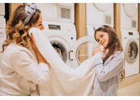 母亲和女儿在自助洗衣店洗衣服_6636892
